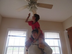 Why get a ladder when an old cheerleading stunt will get Josiah high enough to make room for the Christmas Tree?